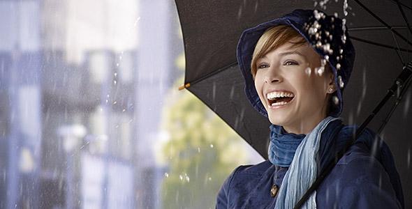 تصویر زن جوان ایستاده زیر چتر و باران