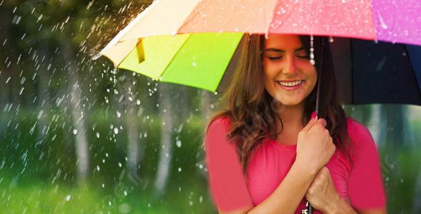 تصویر زن جوان با چتر رنگی زیر باران