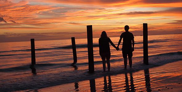 تصویر زن و شوهر در ساحل و غروب آفتاب