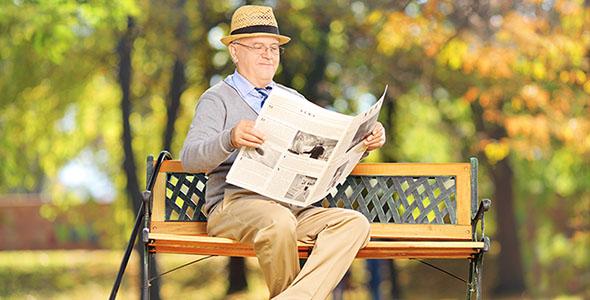 تصویر مرد مسن روی نیمکت چوبی در پارک