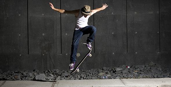 تصویر مرد جوان با اسکیت برد در پیاده رو