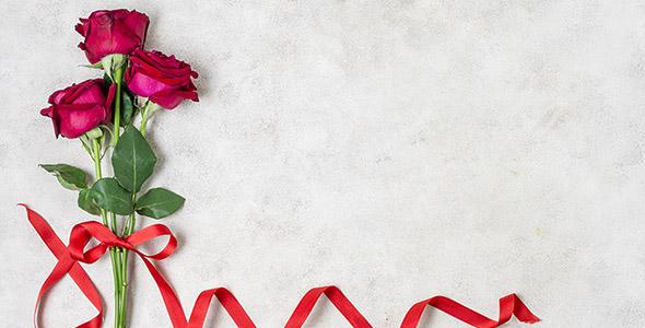 تصویر دسته گل رز و روبان قرمز