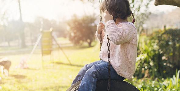 تصویر دختر بچه در حال تاب بازی در پارک