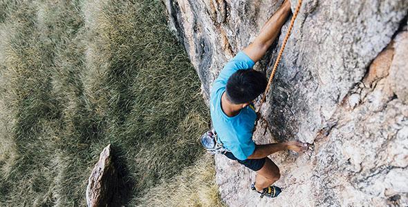 تصویر نمای بالا مرد کوهنورد و صخره نورد