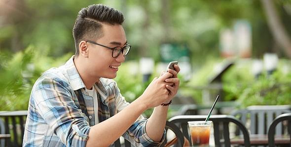 تصویر مرد جوان در کافه و موبایل