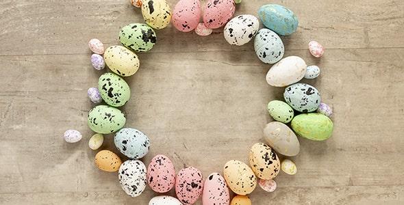 تصویر مجموعه تخم مرغ رنگی روی میز چوبی