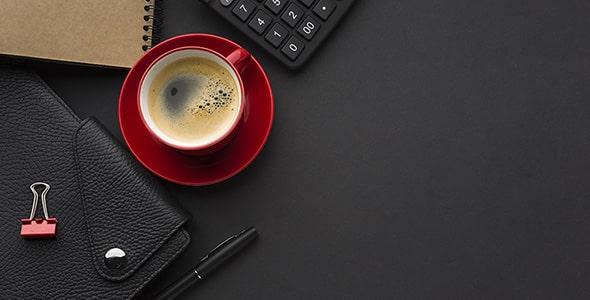 تصویر نمای بالا میز کار با فنجان نسکافه