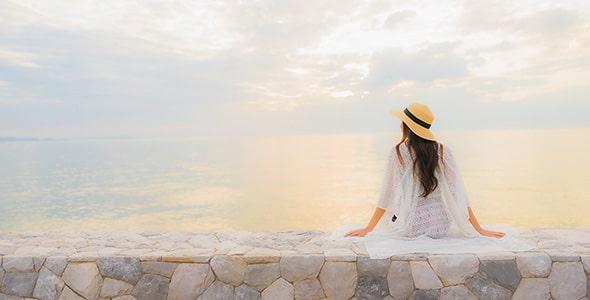 تصویر زن جوان نشسته در ساحل دریا