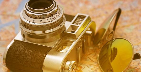 تصویر دوربین قدیمی و عینک آفتابی روی نقشه