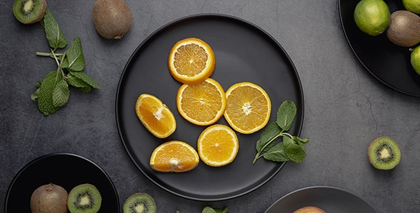 تصویر نمای بالا کیوی و پرتقال با برگ نعنا