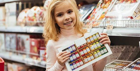 تصویر دختر بچه با لبخند و نگه داشتن شکلات