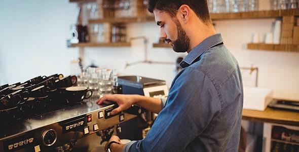 تصویر مرد جوان با دستگاه قهوه ساز و اسپرسو