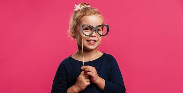 تصویر دختر بچه با لبخند و نگه داشتن عینک