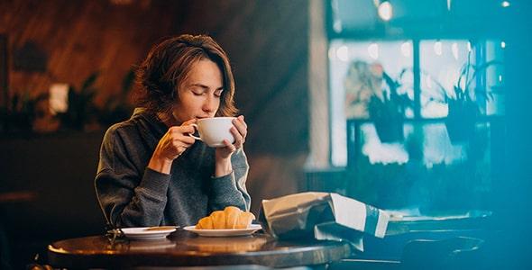تصویر زن جوان در حال خوردن کرواسان و قهوه