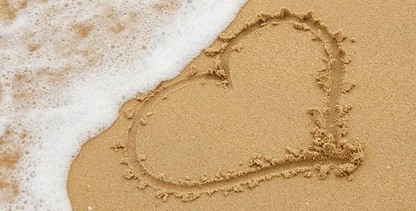 تصویر پس زمینه نقاشی قلب روی ساحل شنی