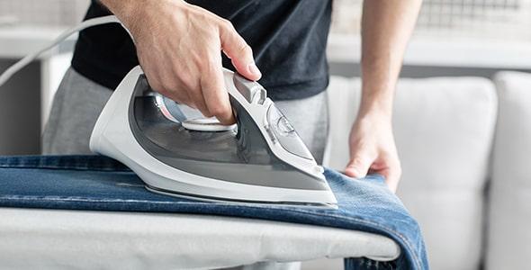 تصویر دست مرد در حال اتو کردن لباس