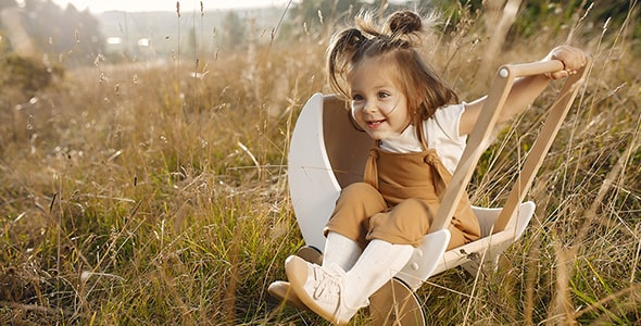 تصویر پس زمینه دختر بچه با کالسکه در پارک