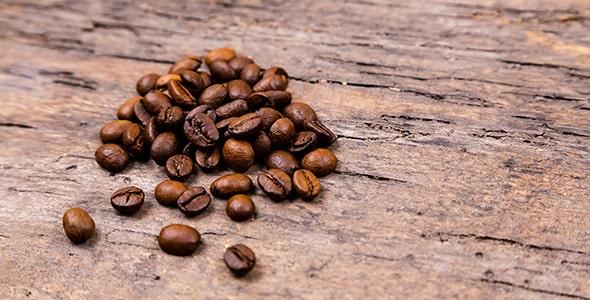 تصویر نمای نزدیک دانه های قهوه روی میز چوبی