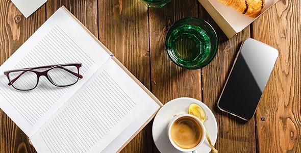 تصویر نمای بالا میز کار با عصرانه و دفترچه