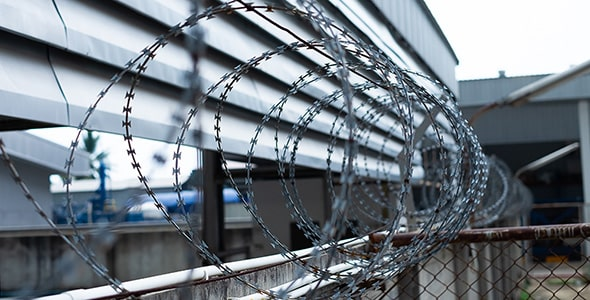 تصویر پس زمینه سیم خاردار و دیوار زندان