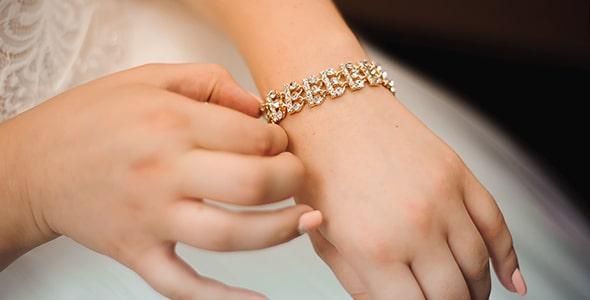 تصویر پس زمینه دست عروس و دستبند طلا