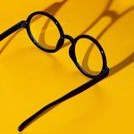 تصویر عینک کائوچویی مشکی گرد در زمینه زرد