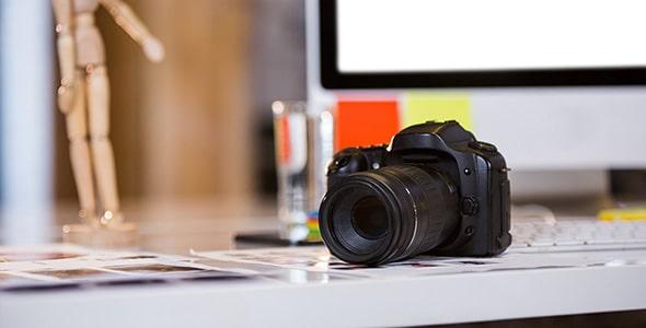 تصویر دوربین عکاسی روی میز کامپیوتر