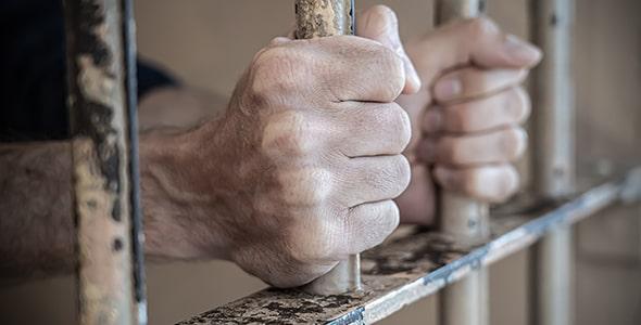 تصویر کلوزآپ دست انسان در زندان و زندانی
