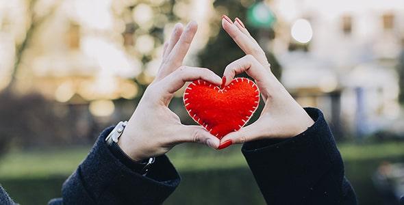 تصویر دست زن و مرد و نگه داشتن قلب قرمز