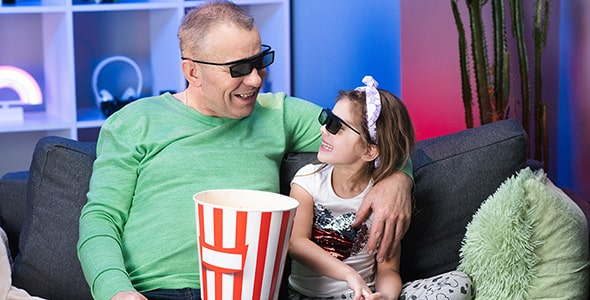 تصویر مرد مسن و دختر بچه در حال تماشای فیلم