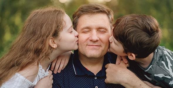 تصویر پسر و دختر بچه در حال بوسیدن پدر