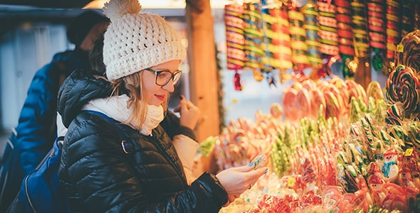 تصویر زن جوان در حال خرید آبنبات در بازارچه