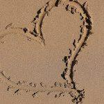 تصویر قلب کشیده شده روی شن و ماسه دریا