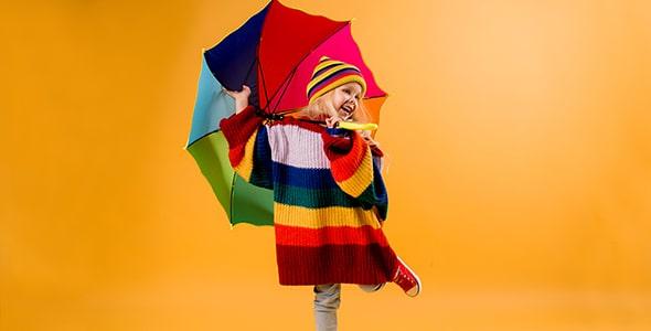 تصویر دختر بچه شاد با ژاکت و چتر رنگارنگ