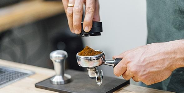 تصویر دست باریستا در حال تهیه قهوه