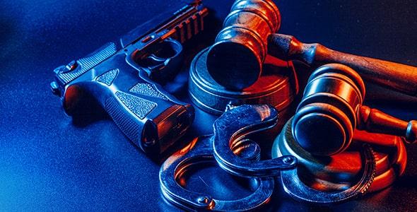 تصویر میز و چکش قاضی با اسلحه و دستبند