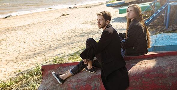 تصویر زن و مرد جوان نشسته در ساحل دریا