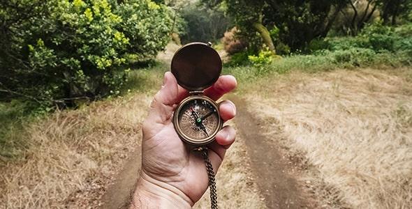 تصویر دست انسان با قطب نما در جاده