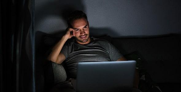 تصویر مرد و تماشای فیلم با لپ تاپ