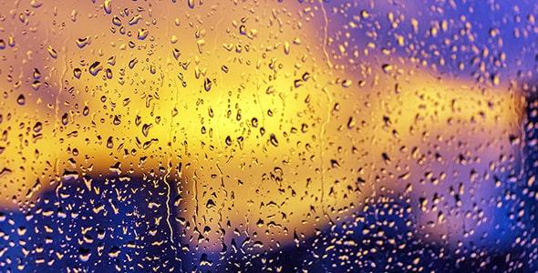 تصویر قطرات باران روی شیشه و غروب آفتاب