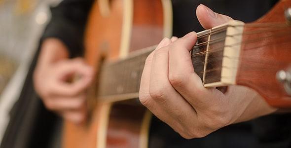 تصویر کلوزآپ مرد در حال گیتار زدن