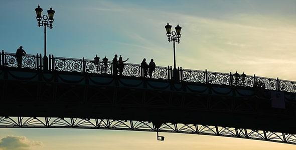 تصویر ضدنور مردم روی پل در غروب آفتاب