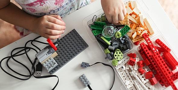 تصویر نمای بالا بچه در حال بازی با لگو