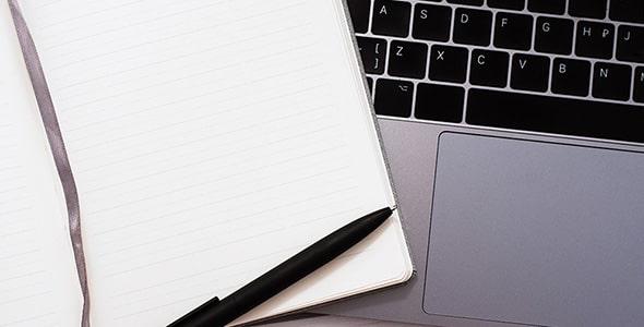 تصویر نمای بالا لپ تاپ و دفترچه یادداشت