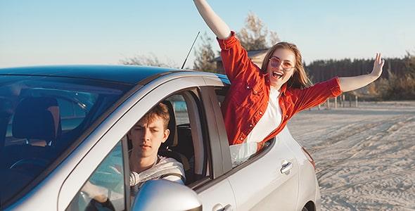 تصویر زن و شوهر جوان با ماشین در ساحل دریا