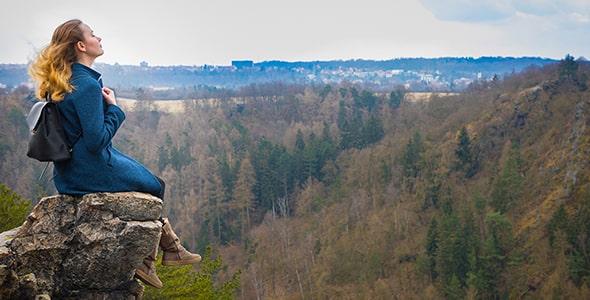 تصویر پس زمینه دختر جوان نشسته در قله کوه