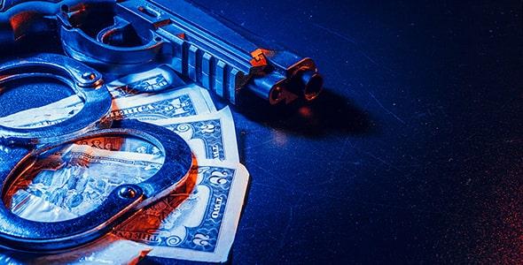 تصویر میز قاضی با اسلحه و دستبند و دلار