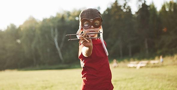 تصویر پسر بچه با کلاه و بازی با هواپیما