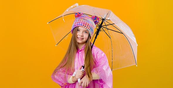 تصویر دختر بچه با کلاه زمستانی و چتر