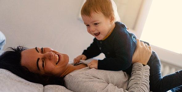 تصویر مادر و بچه در حال بازی در تخت خواب